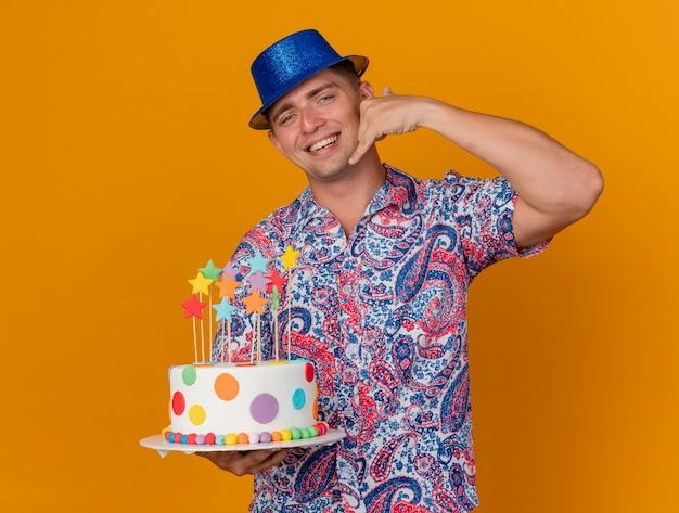 Lächelnder junger partei-typ, der blauen hut hält kuchen hält und telefonanrufgeste lokalisiert auf orange zeigt