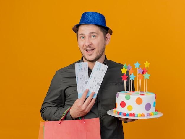 Lächelnder junger partei-typ, der blauen hut hält kuchen mit geschenktüte und tickets lokalisiert auf orange trägt