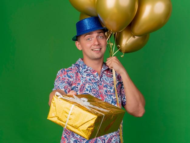 Lächelnder junger partei-typ, der blauen hut trägt, der ballons hält und geschenkbox lokalisiert auf grün hält