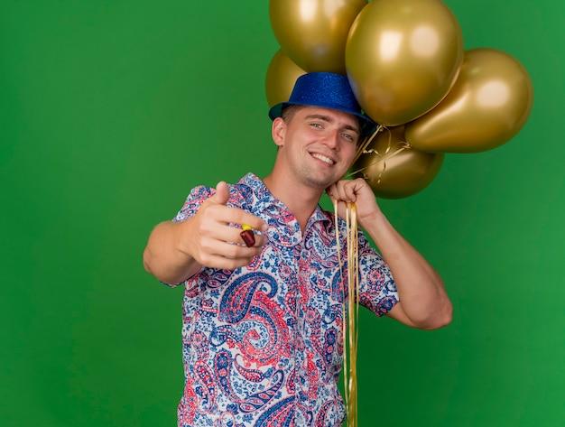Lächelnder junger partei-typ, der blauen hut trägt, der ballons hält und partygebläse hält, das auf grün lokalisiert wird