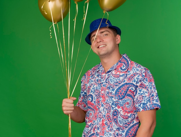 Lächelnder junger partei-typ, der blauen hut trägt, der ballons lokalisiert auf grün hält