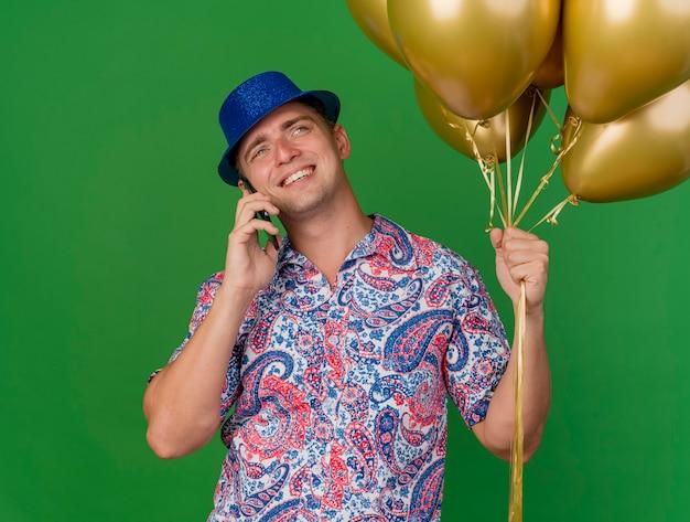 Lächelnder junger partei-typ, der blauen hut trägt, der luftballons hält und am telefon lokalisiert auf grün spricht