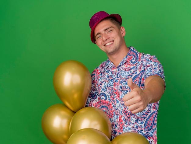 Lächelnder junger partei-typ, der rosa hut hält, der ballons hält daumen oben auf grün lokalisiert