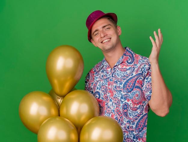Lächelnder junger partei-typ, der rosa hut hält, der ballons hält und hand lokalisiert auf grün anhebt