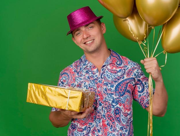 Lächelnder junger partei-typ, der rosa hut hält, der ballons mit geschenkbox lokalisiert auf grün hält