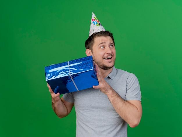 Lächelnder junger party-typ, der geburtstagskappe hält geschenkbox lokalisiert auf grün trägt