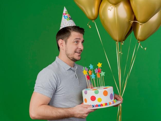 Lächelnder junger party-typ, der geburtstagskappe hält kuchen mit luftballons auf grün isoliert trägt
