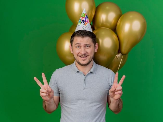 Lächelnder junger party-typ, der geburtstagskappe trägt, die vor luftballons steht, die friedensgeste lokalisiert auf grün zeigen