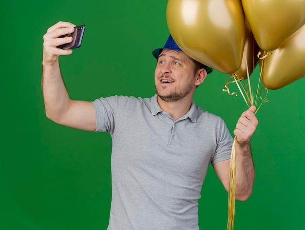 Lächelnder junger party-typ, der partyhut trägt, nimmt ein selfie, das ballons lokalisiert auf grün hält