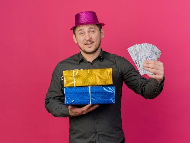 Lächelnder junger party-typ, der rosa hut hält, der geschenkboxen mit bargeld lokalisiert auf rosa hält