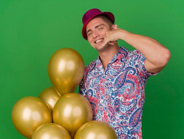 Lächelnder junger party-typ, der rosa hut trägt, der luftballons hält und telefonanrufgeste lokalisiert auf grün zeigt
