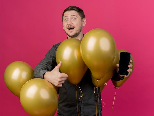 Lächelnder junger party-typ, der schwarzes hemd trägt, das unter luftballons hält telefon hält daumen oben auf rosa lokalisiert