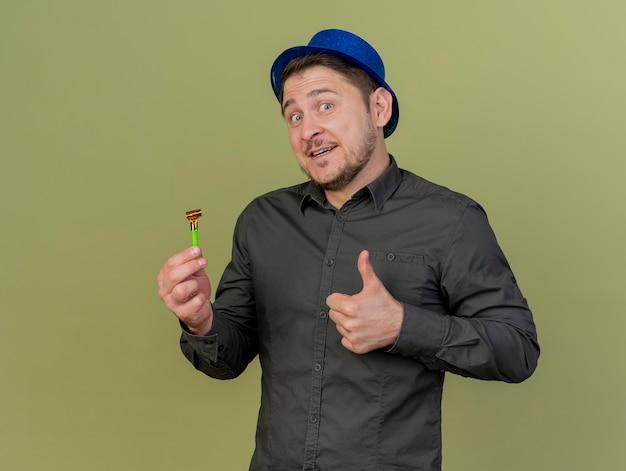 Lächelnder junger party-typ, der schwarzes hemd und blauen hut hält, der party-gebläse hält, das daumen oben auf olivgrün lokalisiert zeigt