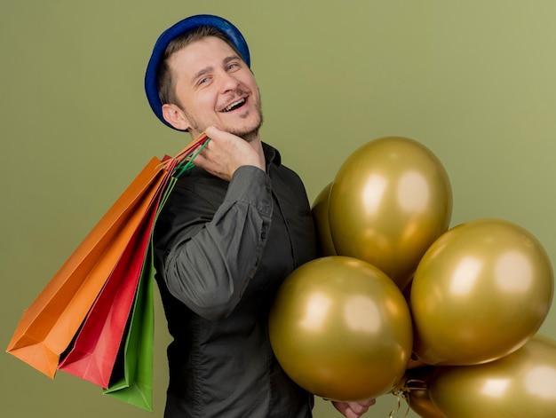 Lächelnder junger party-typ, der schwarzes hemd und blauen hut trägt, der luftballons hält und geschenktüten auf schulter lokalisiert auf olivgrün setzt