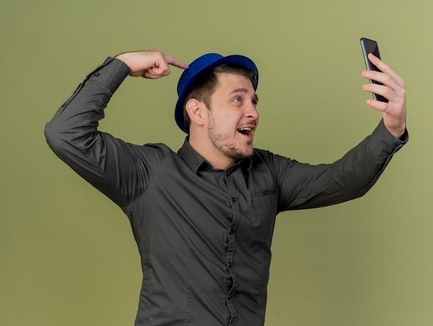 Lächelnder junger party-typ, der schwarzes hemd und blauen hut trägt, nimmt aselfie, der finger auf hut isoliert auf olivgrün setzt