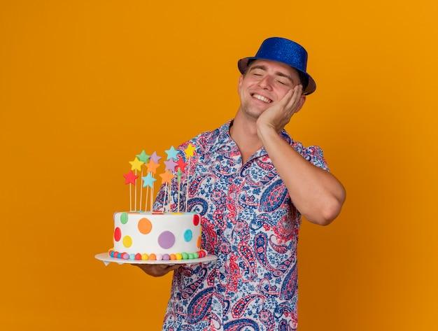 Lächelnder junger party-typ mit geschlossenen augen, der blauen hut hält kuchen hält und hand auf wange lokalisiert auf orange legt