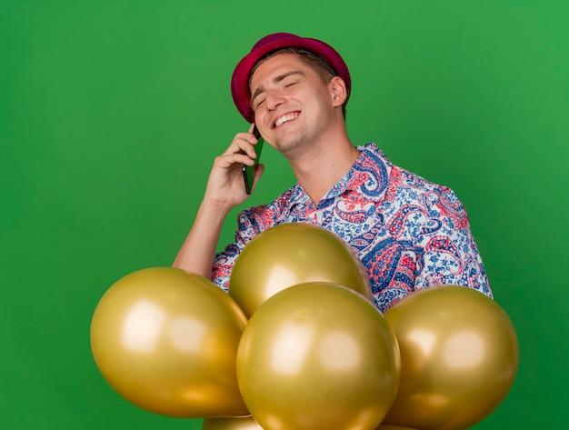 Lächelnder junger party-typ mit geschlossenen augen, der rosa hut trägt, der hinter luftballons steht, lokalisiert auf grün
