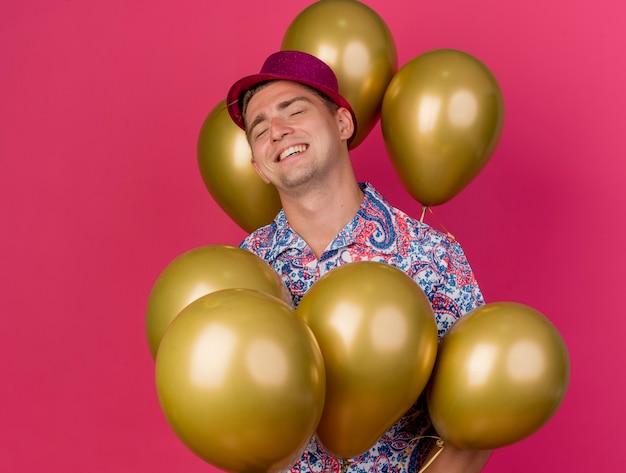 Lächelnder junger party-typ mit geschlossenen augen, der rosa hut trägt, der unter luftballons steht, die auf rosa lokalisiert werden