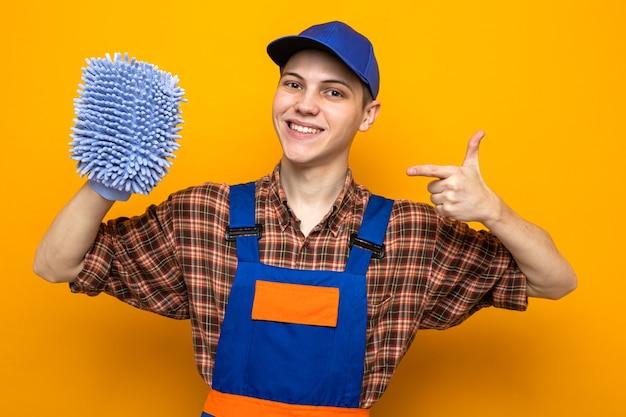 Lächelnder junger putzmann in uniform und mütze hält und zeigt auf lappen