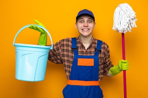 Lächelnder junger putzmann in uniform und mütze mit handschuhen, die mopp und eimer halten
