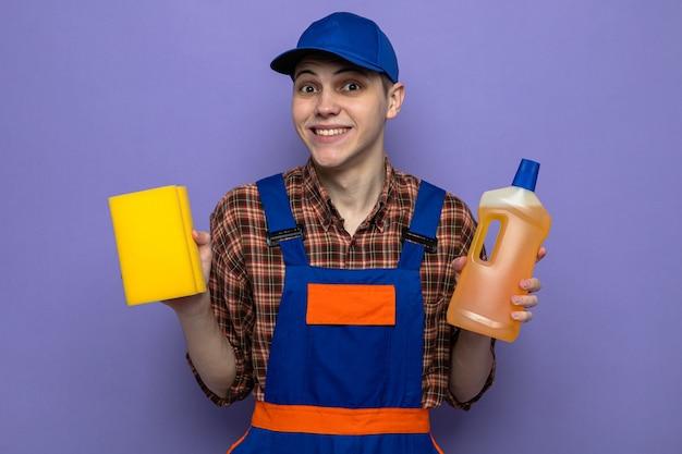 Lächelnder junger putzmann in uniform und mütze mit reinigungsmittel mit schwamm