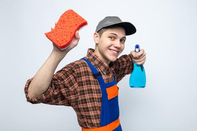 Lächelnder junger putzmann in uniform und mütze mit schwamm mit reinigungsmittel