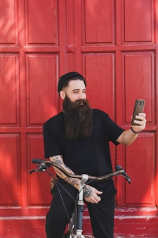 Lächelnder junger radfahrer, der selfie auf seinem smartphone vor roten türen nimmt