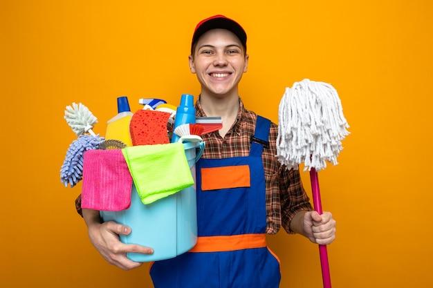 Lächelnder junger reinigungsmann in uniform und mütze, der einen eimer mit reinigungswerkzeugen mit mopp hält