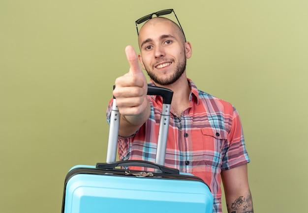 Lächelnder junger reisender mann mit sonnenbrille, der koffer hält und isoliert auf olivgrüner wand mit kopierraum nach oben blättert
