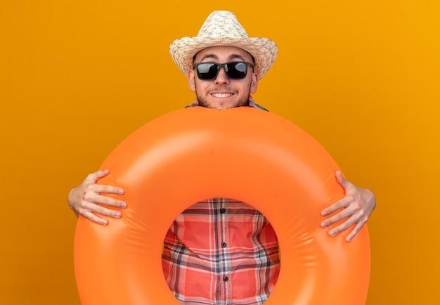 Lächelnder junger reisender mit strohhut in sonnenbrille, der schwimmring isoliert auf oranger wand mit kopienraum hält