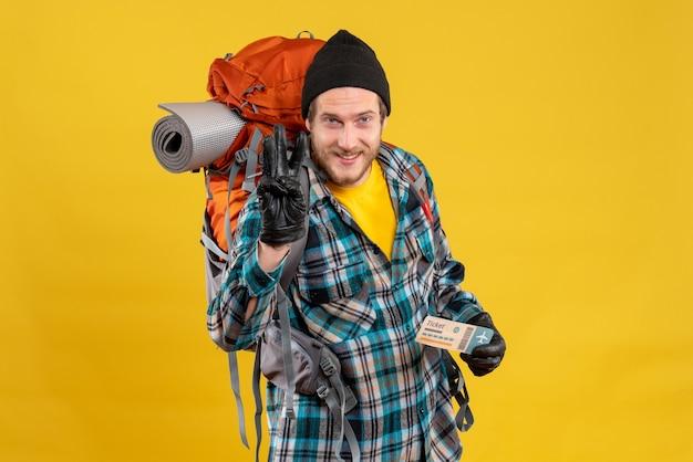 Lächelnder junger rucksacktourist mit schwarzem hut, der ein flugticket mit drei fingern hält
