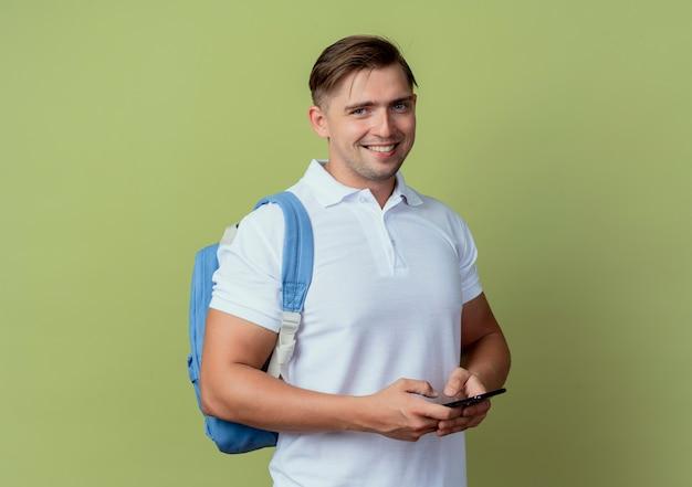 Lächelnder junger schöner hübscher männlicher student, der rückentasche hält telefon lokalisiert auf olivgrün trägt