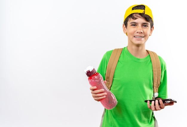 Lächelnder junger schuljunge, der einen rucksack mit einer kappe trägt, die eine wasserflasche mit telefon hält