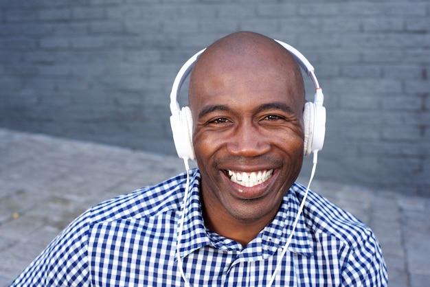Lächelnder junger schwarzer kerl, der musik mit kopfhörern hört