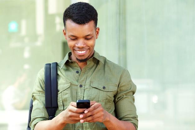 Lächelnder junger schwarzer mann mit intelligentem telefon und rucksack
