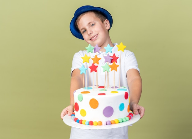 Lächelnder junger slawischer junge mit blauem partyhut, der geburtstagskuchen isoliert auf olivgrüner wand mit kopienraum hält