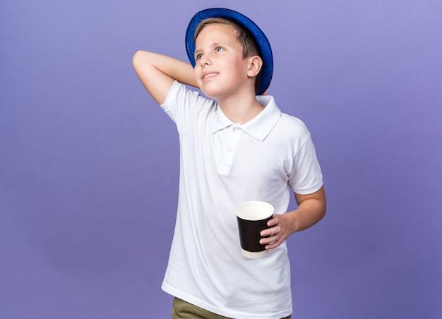 Lächelnder junger slawischer junge mit blauem partyhut, der hand auf kopf hinter sich setzt und pappbecher hält, der seite lokalisiert auf lila wand mit kopienraum betrachtet
