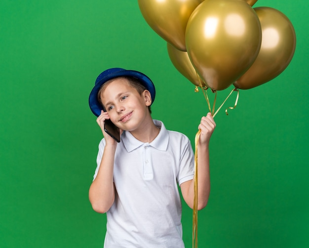 Lächelnder junger slawischer junge mit blauem partyhut, der heliumballons hält und telefoniert, isoliert auf grüner wand mit kopierraum