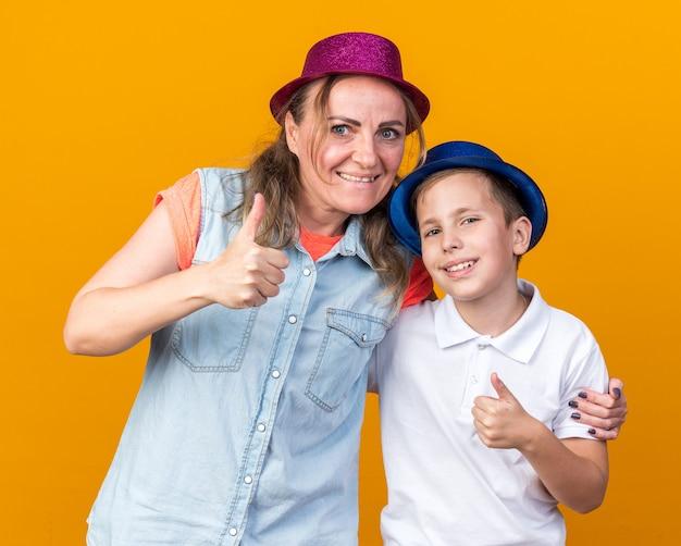 Lächelnder junger slawischer junge mit blauem partyhut, der mit seiner mutter steht, die einen lila partyhut trägt, der isoliert auf oranger wand mit kopienraum nach oben greift