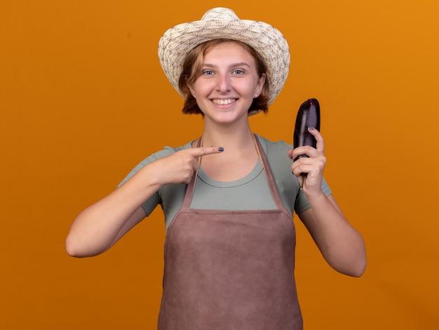 Lächelnder junger slawischer weiblicher gärtner, der gartenhut hält und auf aubergine auf orange zeigt