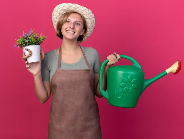 Lächelnder junger slawischer weiblicher gärtner, der gartenhut trägt, hält gießkanne und blumen im blumentopf auf rosa