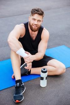 Lächelnder junger sportler mit einer flasche wasser, die draußen sitzt und sich entspannt