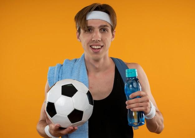 Lächelnder junger sportlicher kerl, der rucksack mit stirnband und armband mit handtuch auf schulter hält wasserflasche mit kugel lokalisiert auf orange wand trägt