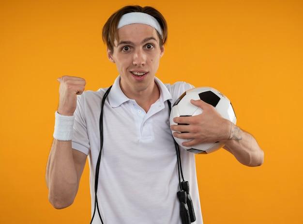 Lächelnder junger sportlicher kerl, der stirnband mit armband mit springseil auf schulter hält ball hält