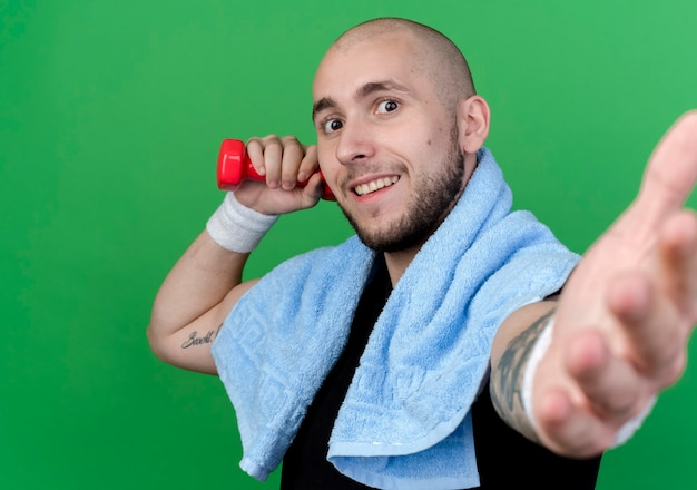 Lächelnder junger sportlicher mann, der armband hält, das hantel mit handtuch auf schulter hält und hand lokalisiert auf grüner wand hält