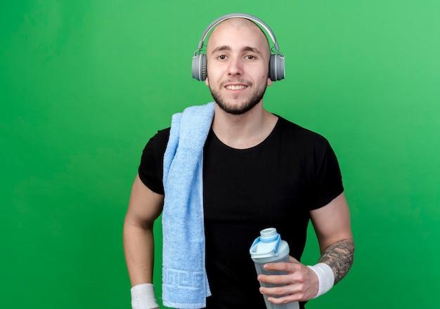 Lächelnder junger sportlicher mann, der armband und kopfhörer hält wasserflasche mit handtuch auf schulter lokalisiert auf grüner wand trägt