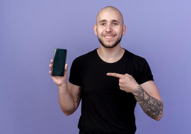 Lächelnder junger sportlicher mann, der hält und auf telefon lokalisiert auf purpur zeigt