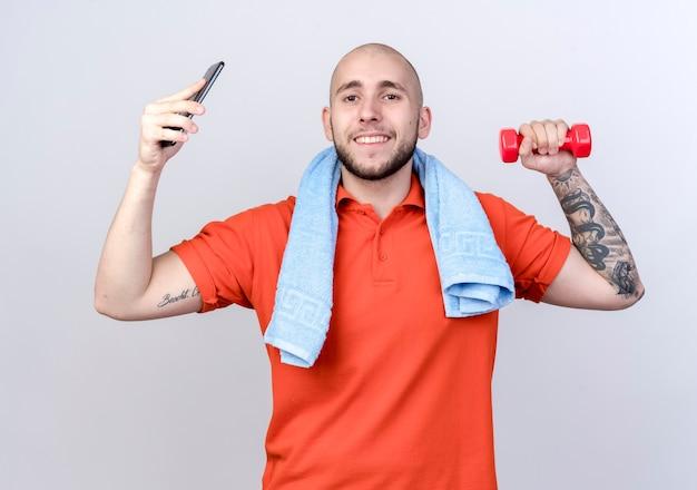 Lächelnder junger sportlicher mann, der hantel mit telefon mit handtuch auf schulter lokalisiert auf weißer wand anhebt