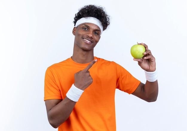 Lächelnder junger sportlicher mann, der stirnband trägt