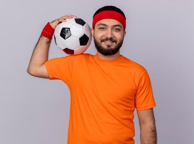 Lächelnder junger sportlicher mann, der stirnband und armband hält ball auf schulter lokalisiert auf weißem hintergrund trägt